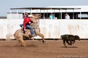 Quincy Wills of Artesia High School dismounts his horse after succesfully roping a calf during the calf roping event.
