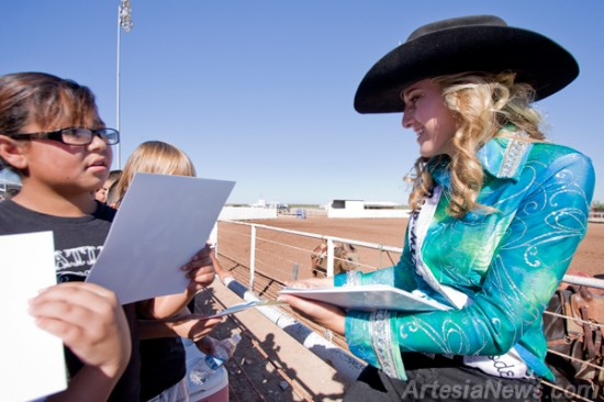 New Mexico State Rodeo Queen Alissa Burson signs autographs for the fourth grade students following the rodeo.