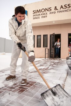 Austin Addington shovels snow from the sidewalk at Simons and Associates on Main Street Wednesday morning.