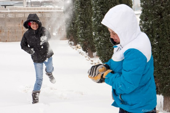 Carlie Reyes, at left, throws a snowball at Erica Reyes in their backyard at the 1000 block of Fourth Street.