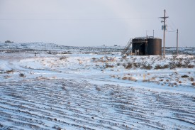 A tank battery sits on top of a snow-covered hill as the sun briefly sneaks out from behind the clouds Wednesday afternoon.