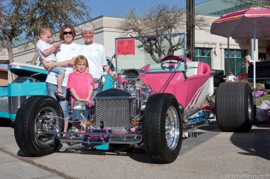 "Megan Lamkin, holding her son Tony, stands next to her mother Lilli Smart and her daughter Fallyn. The family entered Lilli and Dusty Smart's rose-colored T-bucket, ""T-Quila Rose,"" in the 14th annual main event show and cruise Saturday and won first place in its class. Dusty, with help from his family, finished the car only a month before Saturday's show. Lilli explained the custom-built car was put together with a labor of love over two years and three months where Dusty would spend between 30 and 40 hours a week in the garage. See more photos of Saturday's car show on page 8. (Tyler Green – Daily Press)"