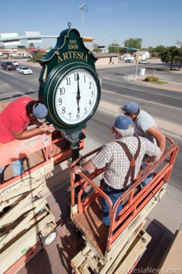 Workers from Perez Construction fasten the town clock to its pedestal at the corner of Seventh and Main Streets on Monday morning. (Tyler Green – Daily Press)