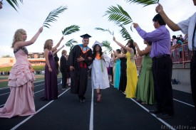 Jeremy De La Rosa and Gabriella Corona walk through an archway of palm leaves on the way to their seats for graduation ceremonies.
