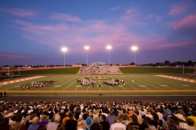 The sky is filled with color over the graduating class as the sun sets behind them.