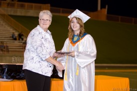 APS School Board Member Carolyn Shearman delivers a diploma to Elizabeth Lewis.