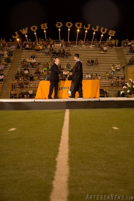 APS School Board President Lowell Irby delivers a diploma to Dylan Romine on the field of the Bulldog Bowl.