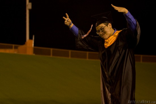Emilio Escamilla, above, holds a peace sign in the air as he approaches the stage to receive his diploma Thursday evening.