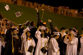 "Graduates celebrate and toss their caps following the AHS ""Alma Mater."""