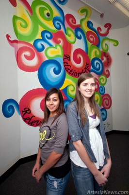 "Artesia Junior High School students Diana Rios, left, and Emily Ferguson stand in front of a mural they recently painted in one of the stairways at the school. The colorful mural includes the school motto, ""Relevance, Relationships and Rigor."" Ferguson explained they spent five hours a day painting the mural over a two week period. ""We began drawing with chalk and it turned into 'this thing.' Also, I was working on calligraphy at the moment and decided to add the school's motto,"" said Ferguson about how the mural transpired. (Tyler Green – Daily Press)"