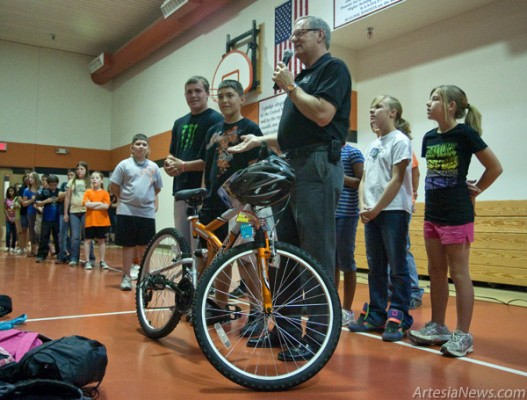 Perry Conner, with microphone, visited Yucca Elementary School this morning to recognize fifth-grade student Tyler Garthwaite for having perfect attendance throughout the past five school years. Conner rewarded him with a 26-inch, 18-speed mountain bike. (Tyler Green – Daily Press)