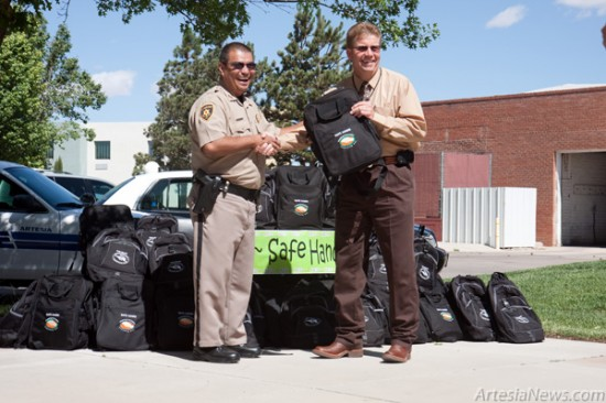 Artesia Drug and Crime Coalition President Robert Smoot, right, hands a Safe Hands backpack to Sheriff's Department Deputy Raul Martinez outside the Chamber of Commerce this morning. Members of the Artesia Police Department, Eddy County Sheriff's Office and New Mexico State Police were given Safe Hands backpacks to be given to children during unsettling circumstances that lead to a child being removed from their home due to drugs, abuse or neglect. With the help of contributions from the community, the Artesia Drug and Crime Coalition was able to implement the Safe Hands program as a way to help law enforcement comfort and support children during traumatic situations. The backpacks are filled with items such as teddy bears, blankets and socks aimed to aid in the transition of these children. (Tyler Green – Daily Press)