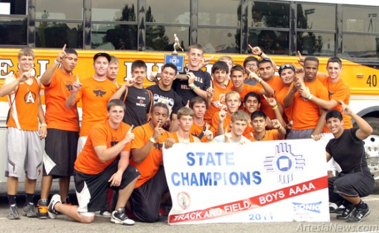 The 2011 Bulldog track and field team poses with its state championship trophy Saturday in Albuquerque. (Brienne Green – Daily Press)