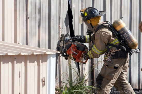 A firefighter uses a saw to gain alternate entrance into a hangar after a fire, apparently ignited by a man using a metal cutting tool inside, broke out at the airport. The man, identified as Joe Perez Moreno III, 29, died in the blaze. (Tyler Green - Daily Press)