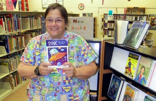 Geri Dosalua holds a children's book in the section of the library where the reading program will be held. (Elizabeth Lewis – Daily Press)