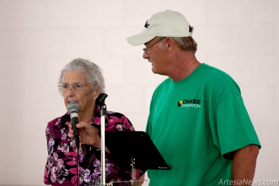 Chase Foundation Director Richard Price holds a microphone for Mary Morgan, who received work from the scholars, as she thanks the scholars for their service.