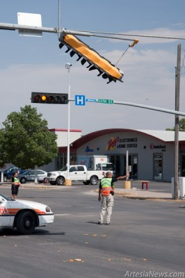 A traffic light at the intersection of 13th and Main streets hangs by a couple of wires after being struck by a passing semitruck pulling a trailer carrying a disassembled pump jack Monday. Artesia Police Department officers directed traffic through the intersection until the damaged light could be put back in place. Robert York, 52, of Hobbs was issued a citation for immediate notice of accident. According to the incident report, York was hauling a large load, approximately 20 feet above the ground, and did not realize he caused the damage. (Tyler Green – Daily Press)