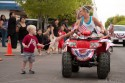 A young woman, right, on a four-wheeler hands a child a miniature American flag during the Fourth of July Parade on Monday.