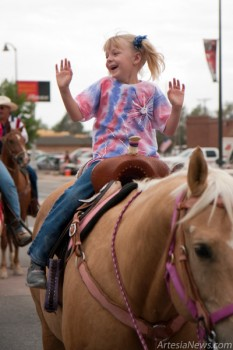 Kyla Van Curen waves with both hands from the saddle of a horse during the parade.