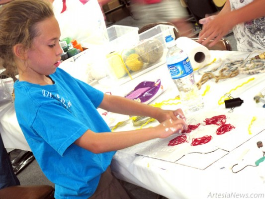 Chloe Yates arranges yarn on her art project during the Artesia Arts Council's Children's 3-D Art Workshop Saturday at the Arts Council Building. Young artists used paint, plaster, string, marbles and other items to create works of art that really popped. See Page 7 for more photos. (Brienne Green - Daily Press)