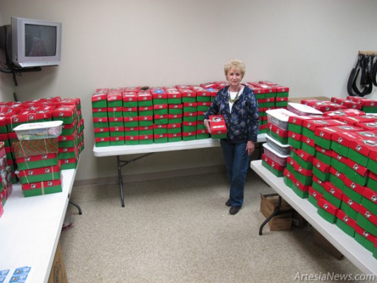 Ruth Bratcher stands in the midst of the stacks of boxes collected in Artesia for Operation Christmas Child. At last count Wednesday afternoon, nearly 600 boxes had been collected toward the goal of 800 boxes. Boxes can be dropped off at First Baptist Church from 1 to 3 p.m. through Saturday, and the boxes will be packed to ship to Roswell at 1 p.m. Sunday. (Jeffrey Heidenreich – Daily Press)