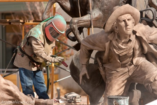A sandblaster removes the patina on The Rustler statue this morning at the intersection of Second and Main streets. The bronze statues around town will be receiving a facelift and a little tender loving care throughout the week. The Rustler will be receiving a new patina, while the other statues will be waxed and buffed. Patina is a tarnish that forms on the surface of bronze and similar metals, produced by oxidation or other chemical processes. Patina is a coating of various chemical compounds such as oxides or carbonates formed on the surface during weathering. The Statue of Liberty gets its green color from the natural patina formed on its copper surface. (Tyler Green – Daily Press)