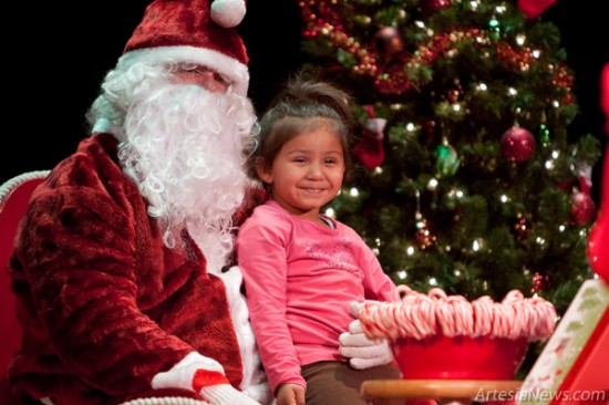 4-year-old Arianna Rodriguez poses for a picture with Santa Claus Thursday at the Ocotillo Performing Arts Center. Rodriguez, one of numerous children that queued at the Ocotillo to deliver their wish lists, asked Santa for a Barbie house for Christmas. Despite frigid temperatures and a stiff wind, the turnout was strong for Light Up Artesia. (Tyler Green photo)