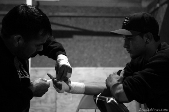 Anselmo Martinez wraps the hands of Zach Hernandez of Lubbock, Texas before his 145-pound bout against Dominic Salmon of Artesia. Dominic won the fight.
