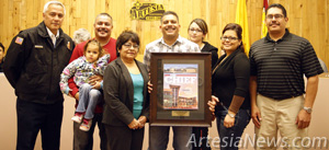 "Artesia Fire Department Chief J.D. Hummingbird presents a plaque with the cover of Fire Chief Magazine featuring the Artesia Public Safety Complex to the family of former Artesia Mayor Manuel Madrid. Hummingbird explained when he came to Artesia in July of 2006, Mayor Madrid asked him to accomplish two things: to revamp the early warning system and to design a new fire station. ""It was his vision and his leadership that led to this building,"" Hummingbird said. ""Not only was it his vision that led to this building, it was recognized nationally."" The plaque reads, ""In commemoration of his vision, leadership and commitment to the citizens of the City of Artesia."" The PSC won a Gold Award for shared facilities along with being featured on the cover of the magazine. Pictured above from left are Hummingbird, Todd Madrid holding Adriana Madrid Montoya, Linda Madrid, Bryan Madrid, Michelle Madrid Montoya, Katrina Madrid and Manuel Madrid Jr."
