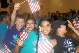 From left, J.W. Necaise, MiRaena Dominguez, Victoria Torres and Jessie Watts excitedly wave their flags following a Flag Day celebration Friday at Yeso Elementary School. Yeso third-graders sang patriotic songs, and the Downtown Lions Club donated an American flag to each child at the school. Courtesy Photos