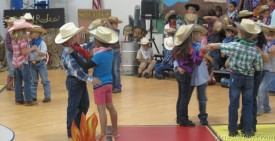 Students from Grand Heights Early Childhood Center two-step around the gymnasium this morning during a program celebrating the American cowboy. Jackie Foster - Daily Press
