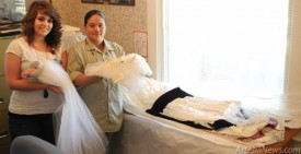 Kelcey McCaleb, left, and Yvette Duarte display a few wedding dresses recently donated to the Artesia Historical Museum and Art Center. The first wedding dress was worn by a bride during World War II, while the other, worn by the war bride's daughter, was made for a wedding in 1970. Rob Larson – Daily Press