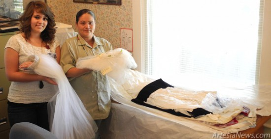 Kelcey McCaleb, left, and Yvette Duarte display a few wedding dresses recently donated to the Artesia Historical Museum and Art Center. The first wedding dress was worn by a bride during World War II, while the other, worn by the war brides daughter, was made for a wedding in 1970. Rob Larson  Daily Press