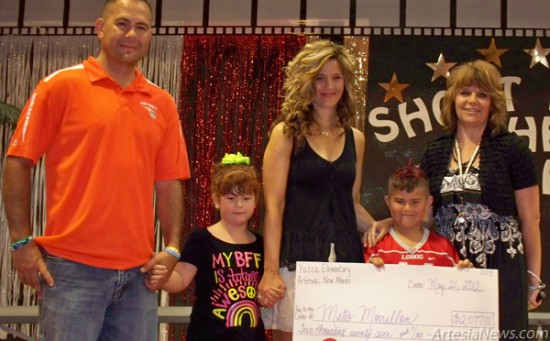 Yucca Elementary School first-grader Mateo Morillon, surrounded by his family, receives a check for more than $2,000 raised by Yucca students through an M&M sale. The students organized the fundraiser to aid Morillon with expenses related to his cancer treatment in Houston. Courtesy Photo
