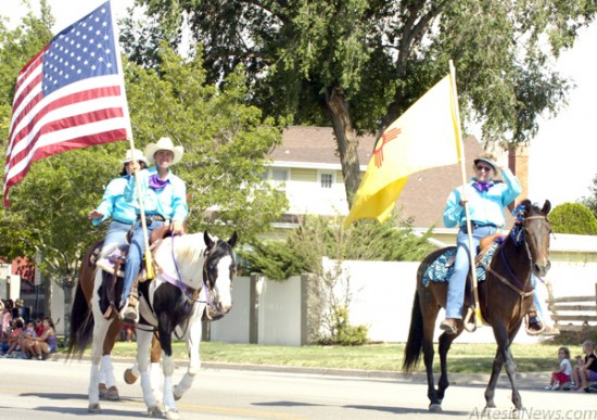 The American and New Mexico flags are carried down Main Street Monday afternoon during the annual Eddy County Fair Parade. Brienne Green - Daily Press