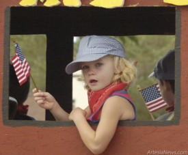 A young parade participant waves her American flag at spectators. Artesians turned out in droves for the parade. Brienne Green - Daily Press