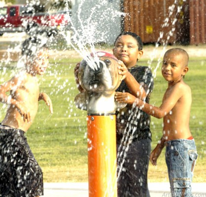 A group of children enjoy the Splash Pad at the Martin Luther King Jr. Recreation Complex during the annual Back to School Bash event Thursday afternoon. Brienne Green - Daily Press