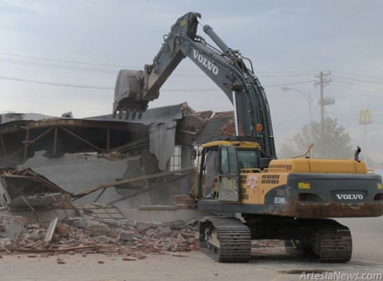 A Sweatt Construction crew finishes demolishing the old brick building at Second Street and Quay Avenue this morning. The building was formerly a NAPA auto parts store and small engine repair shop. The property, owned by Bennie's Western Wear owner Jimmy Mason, was sold to First American Bank and will become the bank's new parking lot. In turn, the bank's old parking lot, located across Quay Avenue, will soon be the site of the new Artesia Public Library. Rob Larson – Daily Press