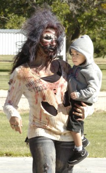 A zombie mom makes her way toward vendors set up at Jaycee Park during the inaugural Eddy County Thrill the World and Zombie Walk Saturday afternoon at Jaycee Park. Zombies of all ages and states of deterioration enjoyed the walk, activities and Thrill the World dance, with proceeds from the event benefitting Big Brothers/Big Sisters. Brienne Green - Daily Press