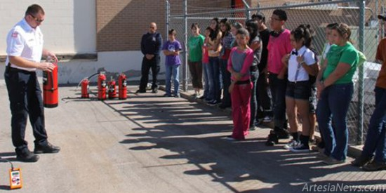 Artesia Fire Marshal James Abner demonstrates proper fire extinguisher use to home-ec students at Park Junior High Wednesday.