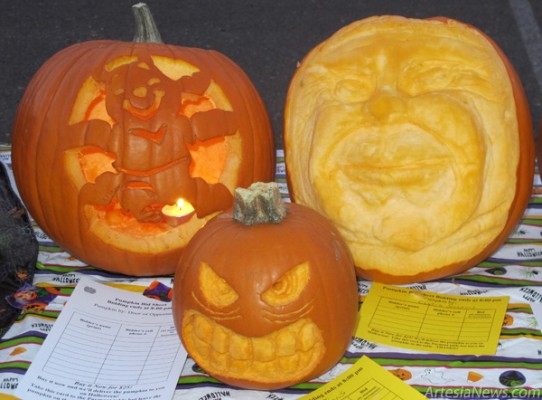 Several carved faces leer at bidders Tuesday at the Boy Scouts' annual Pumpkin Glow event. The faces, carved by Chris Simons, received Golden Pumpkin awards. Also pictured above is a Winnie the Pooh pumpkin by the Door of Opportunity.  Rob Larson - Daily Press