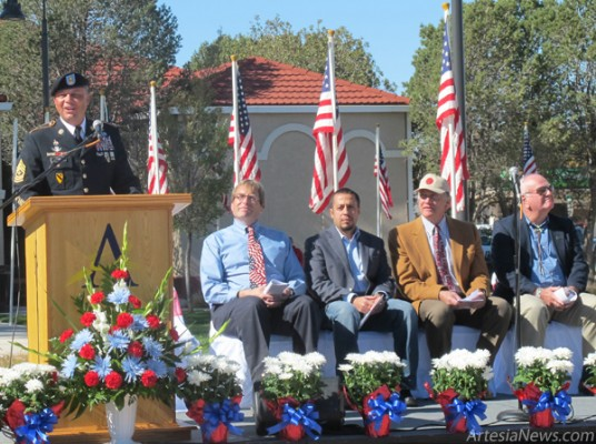 Sgt. Major William Fisk, an Artesia native and keynote speaker for the Baish Veterans' Park dedication, addresses the audience Monday at the park. Fisk was joined on stage by, from left, Gene Dow, vice president and manager of KSVP; Jose Zelaya, Baish Veterans' Park's architect; Peyton Yates, president of Artesia MainStreet; and Mayor Phil Burch.