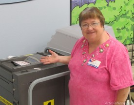 "Alice Smith, volunteering at the polling location at Central Elementary School, stands next to the tabulator. Smith said voters had been coming in to vote ""in spurts"" all morning. Polls will be open until 7 p.m. today. Voters needing information on their polling place should visit www.voterview.state. nm.us. Rob Larson - Daily Press"