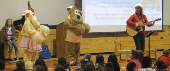 "Students at Yucca Elementary School sing along to ""Rudolph the Red-Nosed Reindeer"" this morning at the school's holiday singalong as Lynn Sundheimer plays guitar and Rodney (Mrs. Garthwaite) and Rhonda (Mrs. Fodge) Reindeer dance to the music. Christina Pizarro - Daily Press"