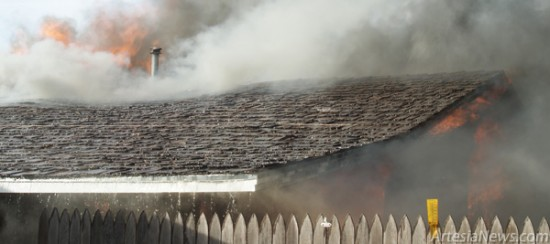 Smoke pours from the attic of the residence  at 2709 W. Grand Ave.  Courtesy Photo