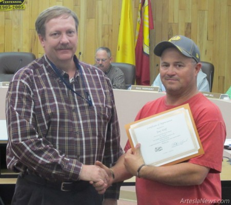 Infrastructure Director Byron Landfair, left, awards city employee Tony Wolf a certificate recognizing his 10 years of service to the community during Tuesday's council meeting. Rob Larson – Daily Press