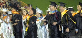 High winds and a touch of rain Thursday night at Bulldog Bowl can't dampen the spirits of the Artesia High School Class of 2013. Seniors locked arms for one final singing of the AHS Alma Mater near the conclusion of the ceremony. Samantha Morin - Daily Press
