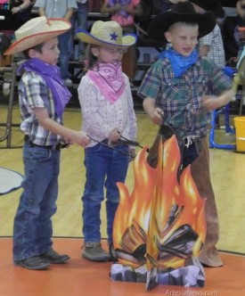 Above and at left, students at Grand Heights Early Childhood Center cook up western-themed fun at the school's Cowboys Round-Up. Kindergarteners performed songs, dances and skits for a delighted audience of staff and    parents. Grace Miller - Daily Press