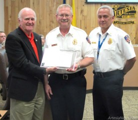 Rick Burks of the Artesia Fire Department, center, is presented with a certificate by Mayor Phillip Burch in appreciation of his 20 years of service with the AFD at Tuesday's city council meeting as Fire Chief J.D. Hummingbird looks on. Brienne Green - Daily Press