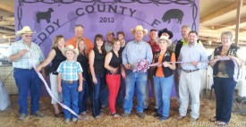 To kick off the 2013 Eddy County Fair members came together for a ribbon cutting.  From left to right on the back row:County Commissioner Royce Pearson,ECFB Director Lance Conklin holding daughter Klanclie, age 2, County Commissioner Glenn Collier, ECFB Directors, Jerry Harrison, and Trail Blazer Jessie Brownfield. Front Row: ECFB Director Johnny Waldrip, Chamber of Commerce Representatives Vickie Grousnick, Brice Bain, Debbie Reed, Kelci McCaleb, Hayley Klein, EC Fair Board President John Bain,Trail Blazer Linda Newberry, ECFB Director Justin Montgomery, , and Trail Blazer President Susie McCaw.  Not Pictured: ECFB Treasurer TJ Harrison, ECFB Director Toby Reed, EC Fair Board Vice President Vance Parrott, and Secretary Kevin Klein. Grace Miller – Artesia Daily Press